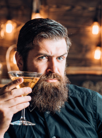 Retro bar. Bearded man sitting at bar. Handsome man drinking olcohol while sitting at the bar.